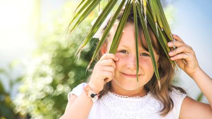 Mädchen hinterm Palmenblatt