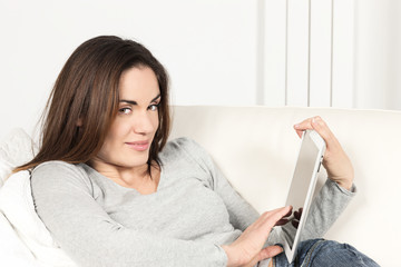 woman with tablet on sofa