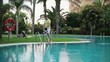 Family by the hotel swimming pool, steadicam shot