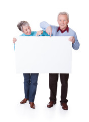Senior Couple Holding Blank Placard