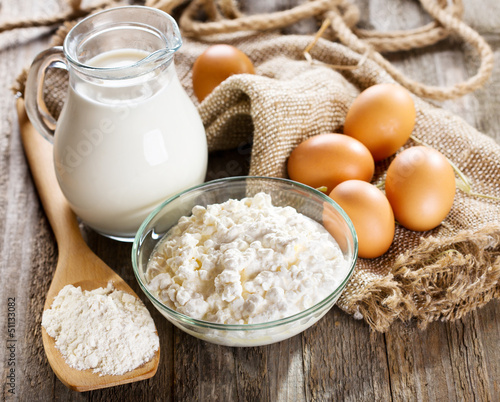 milk, cottage cheese, eggs and flour on wooden table