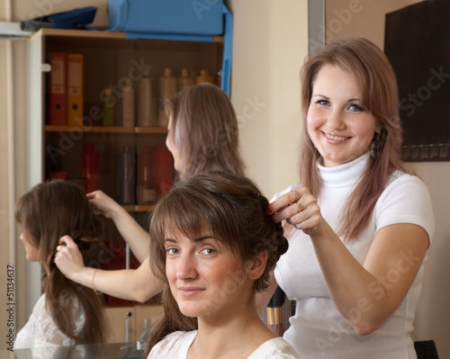 hairdresser works on woman hair