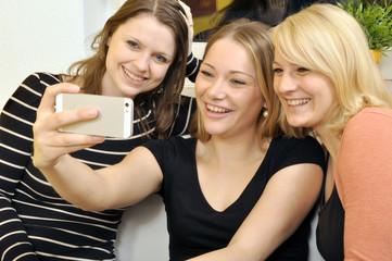 Junge Frauen fotografieren sich mit Smartphone