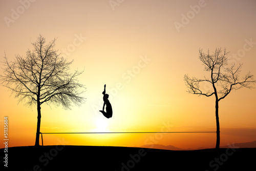 silhouette of girl jumping on slackline in sunset