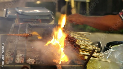 Hawker Grilling Satay over Barbecue Pit Open Flames in Singapore