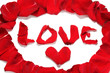 """""""Love"""" lined with red rose petals isolated on white"""