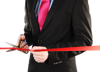 Man's hand cutting red ribbon with pair of scissors for