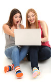 Two girl friends with with laptop isolated on white