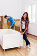 Young couple measuring the sofa in their new apartment