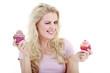 Junge Frau überreicht augenzwinkernd lächelnd Cupcake