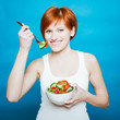 young happy woman eating salad