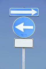 Segnale stradale con frecce su cielo blu