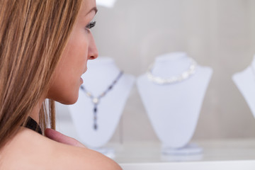 Young Woman Looking At Necklace