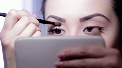 Young woman with mirror and makeup brush.