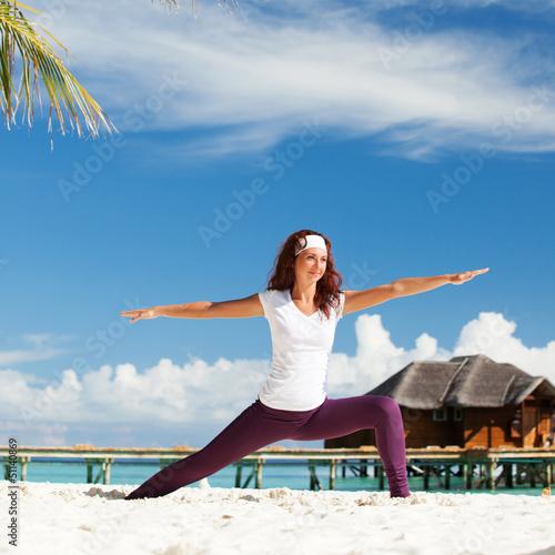Pretty woman doing yoga exercises on the beach