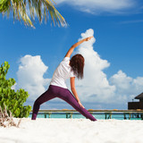 Pretty woman doing yoga exercises on the tropical  beach