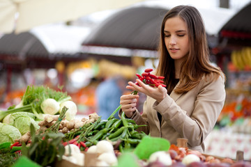Young woman buying red hot chilli peppers at the market