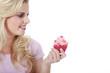 Junge hübsche Frau mit Cupcakes lacht und blickt auf Feld