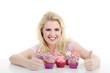 Junge hübsche Frau mit Cupcakes lacht Daumen hoch