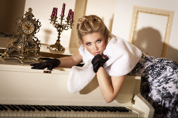 Beautiful blonde woman in fur with grand piano
