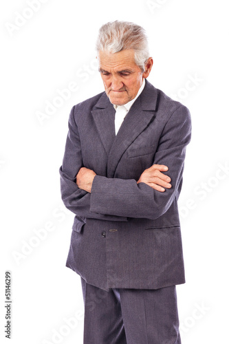 Elderly man with arms folded looking down lost in deep thought