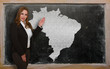 Teacher showing map of brazil on blackboard
