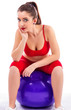 Beautiful young woman relaxing on big mauve exercise ball