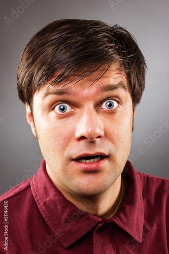 Young handsome man with astonished expression