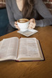 Young Woman with White Coffee Cup Reads Her Bible