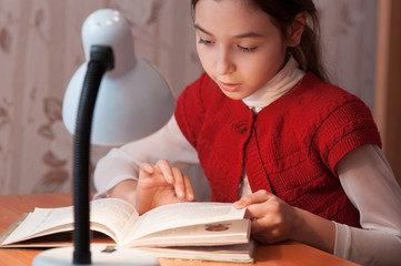 girl at desk reading a book by light of the lamp