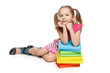 Smiling little girl sitting on floor leaning on stack of books