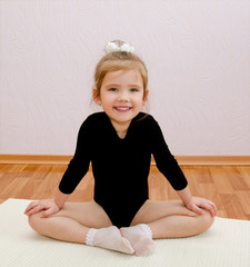 Gymnast smiling little girl doing exercises