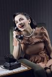 Happy woman talking on landline phone