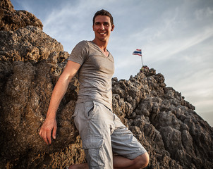 Portrait of smiling adult handsome man against rock background.
