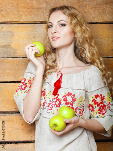 Woman in traditional dress holding apples in her hands