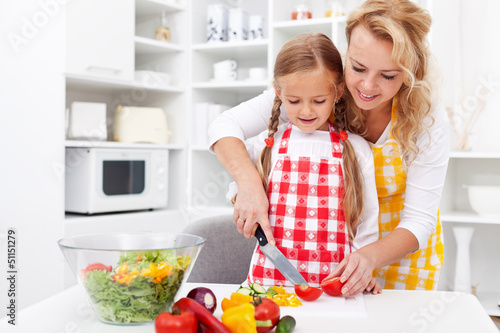 Woman and little girl preparing a vegetables salad