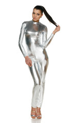 Futuristic young woman in silver clothing in full length