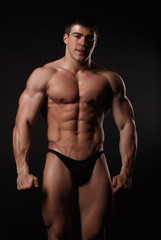 Young attractive man in a black bathing suit bodybuilder