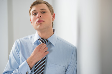 Portrait of a successful young business man adjusting neck tie