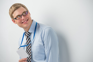 Happy smiling business man showing blank badge, while leaning on