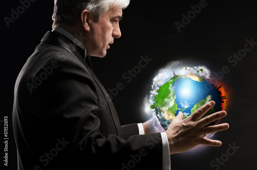 Senior business man holding planet in his arms and controlling i