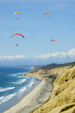 Formation of Four Hang Gliders Above Ocean and Cliffs