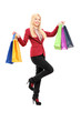Full length portrait of a blond smiling woman holding shopping b