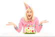 Smiling birthday female wearing party hat and gesturing