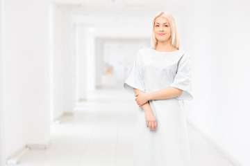 Female patient wearing hospital gown and posing in a hospital