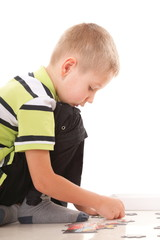 child boy playing puzzle isolated