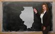 Teacher showing map of illinois on blackboard