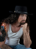 Tough sexy man with long hair and a cowboy hat