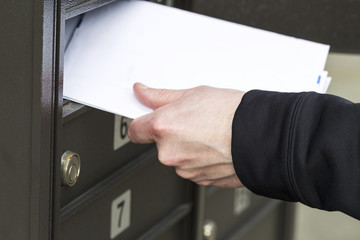 Man getting letters from postal mailbox