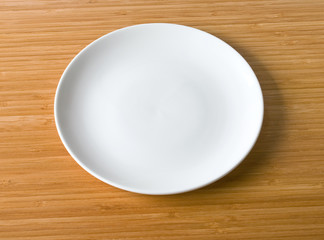 white plate on a bamboo table top